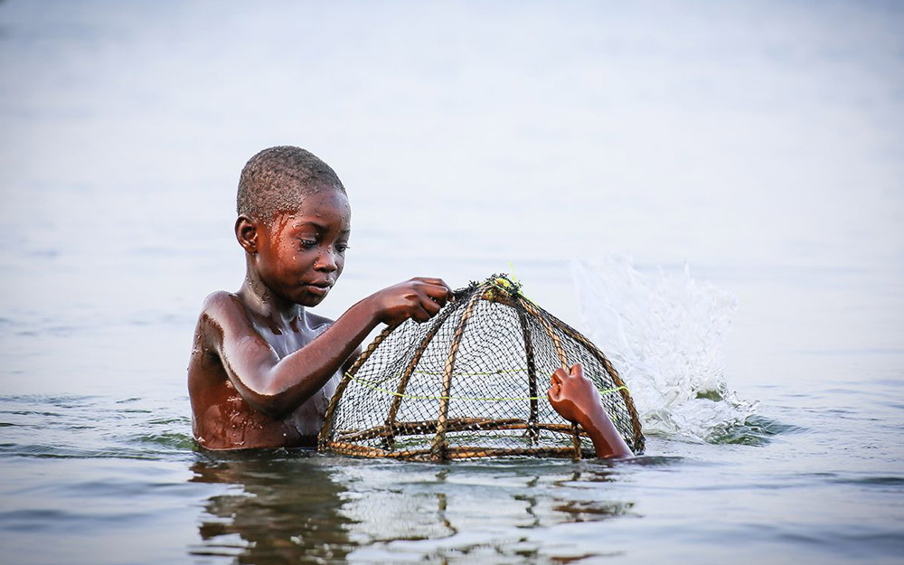 young boy working in water
