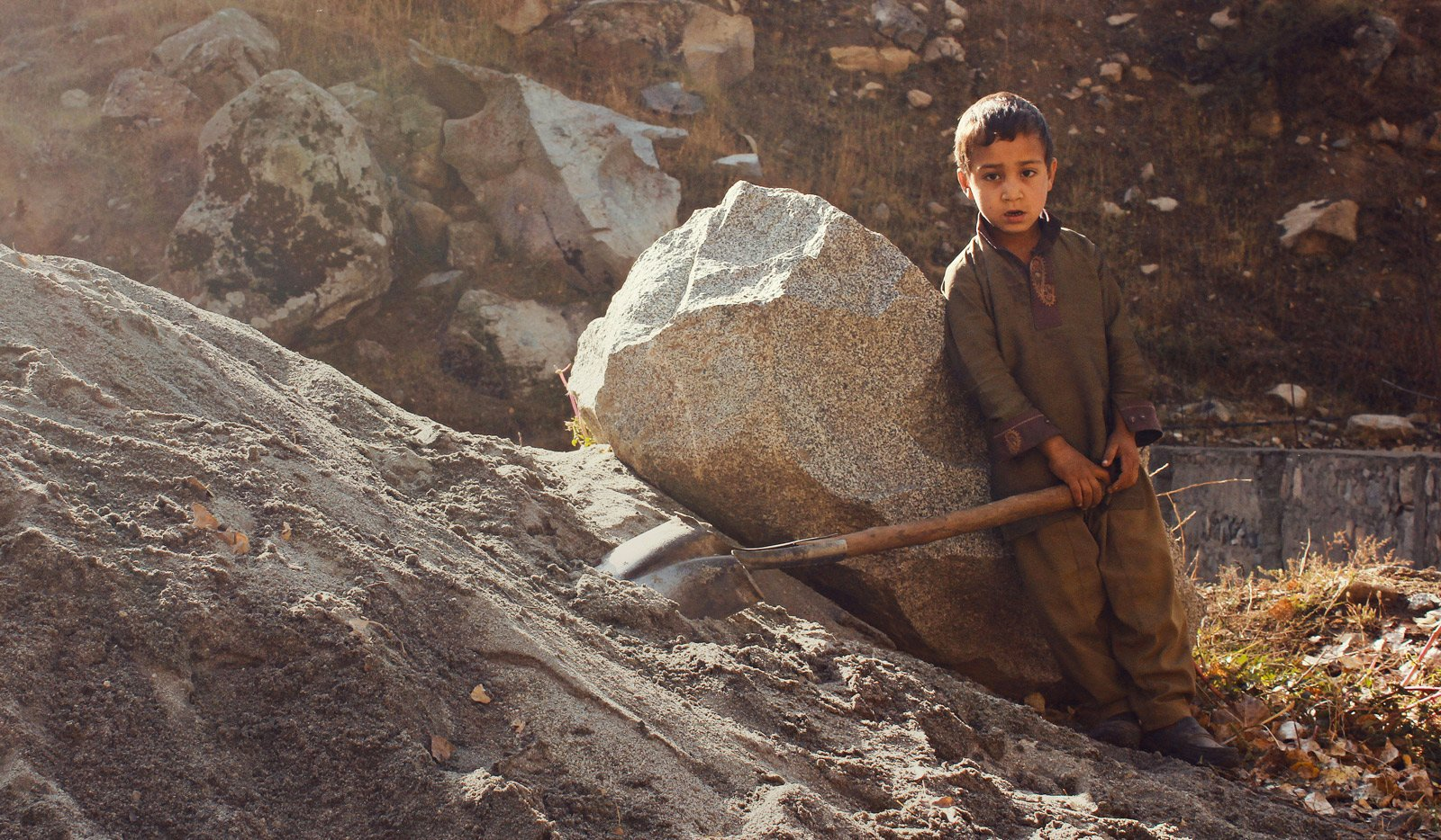 boy with shovel rests while working in valley