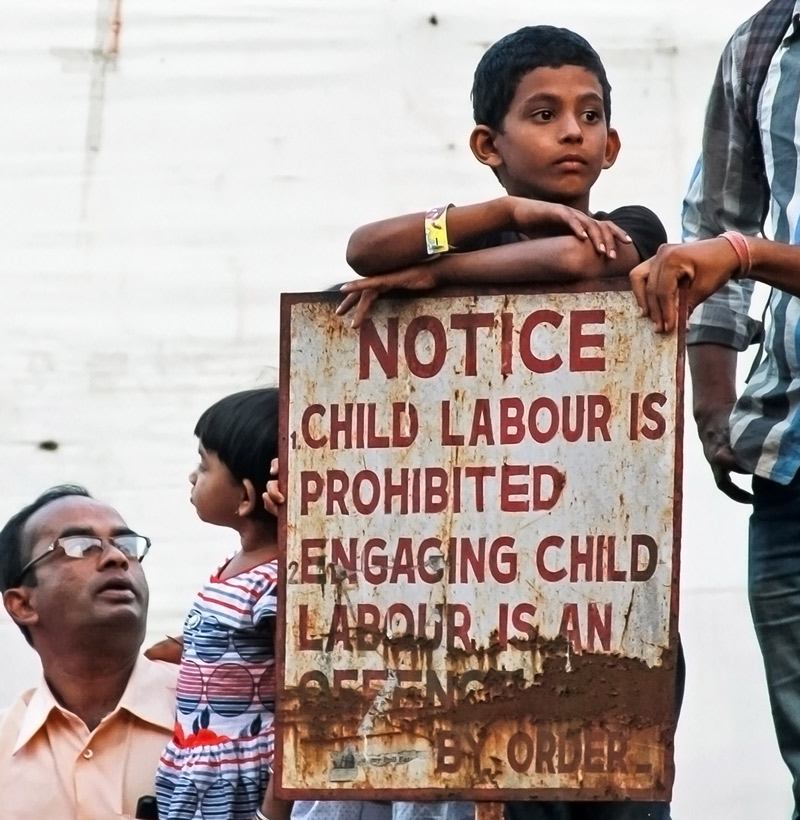 children stand by a sign against child labor