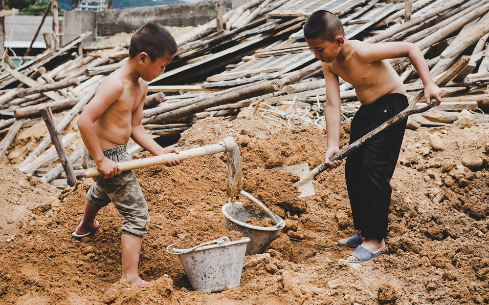 young boys working construction digging dirt