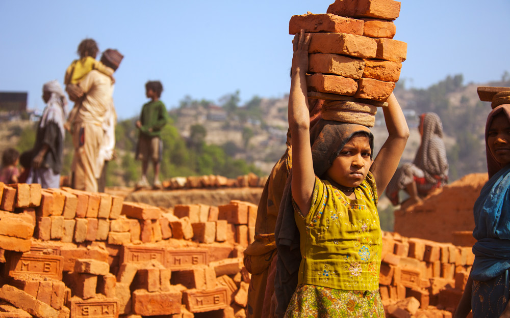 young girl carrying bricks on her head