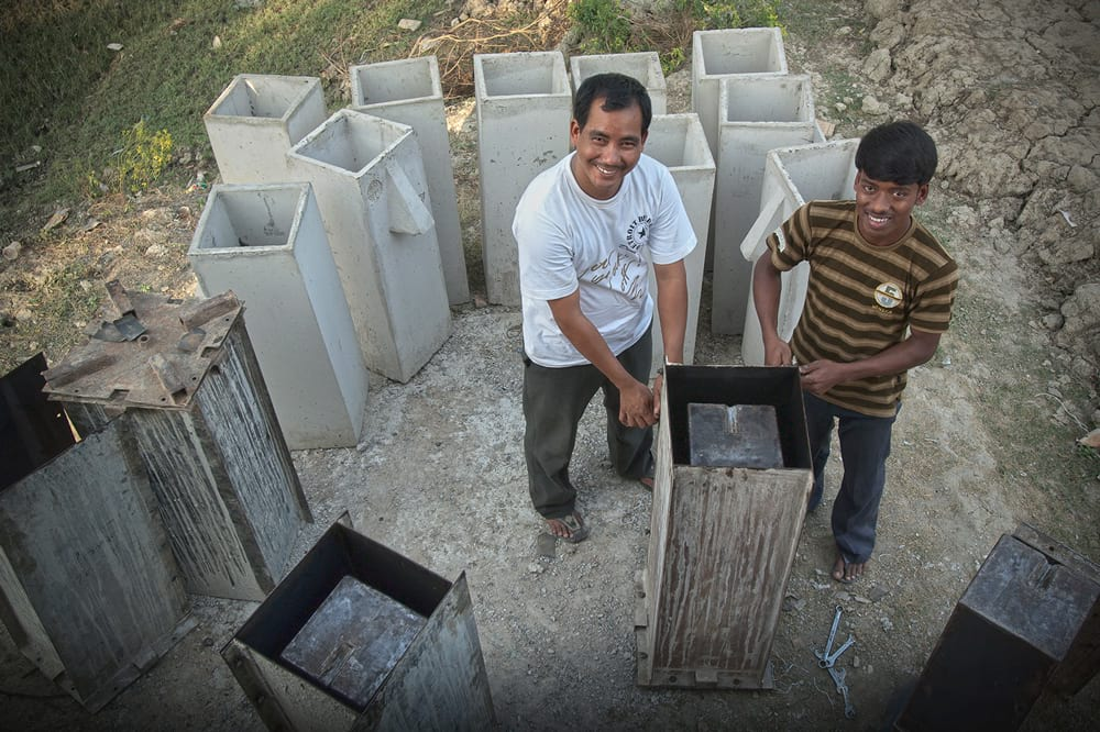 Two men building BioSand Water Filters
