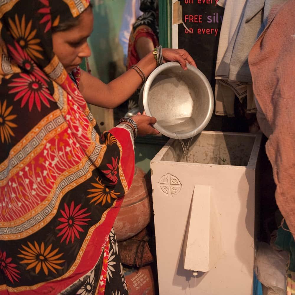 Woman filtering water through BioSand Water Filter