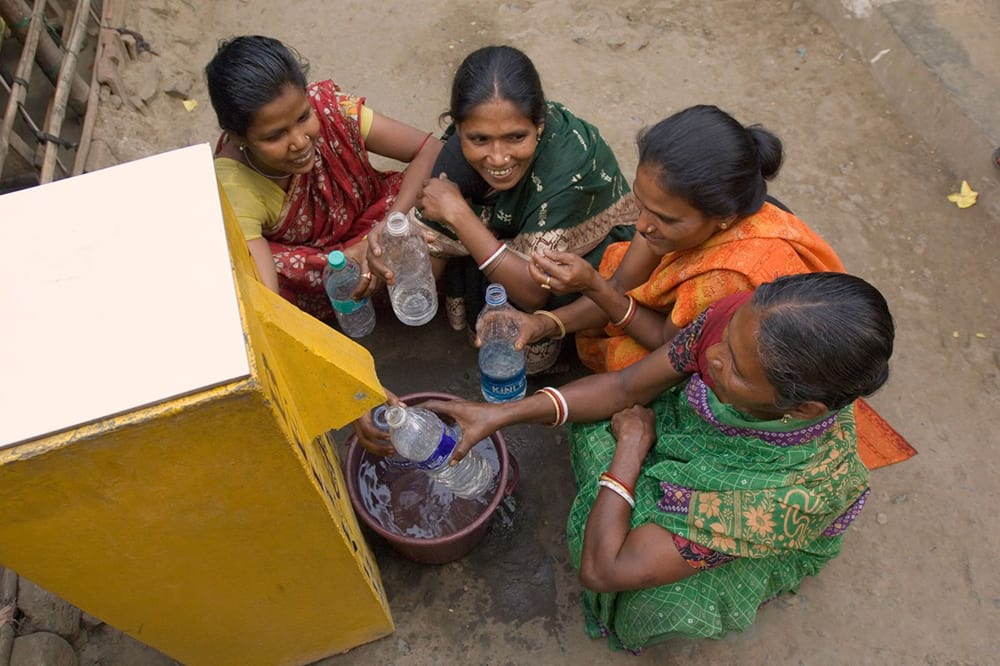 Women filling up water bottles using BioSand Water Filter