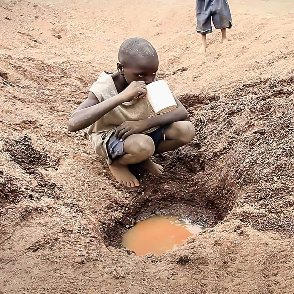 Boy drinking dirty water from puddle