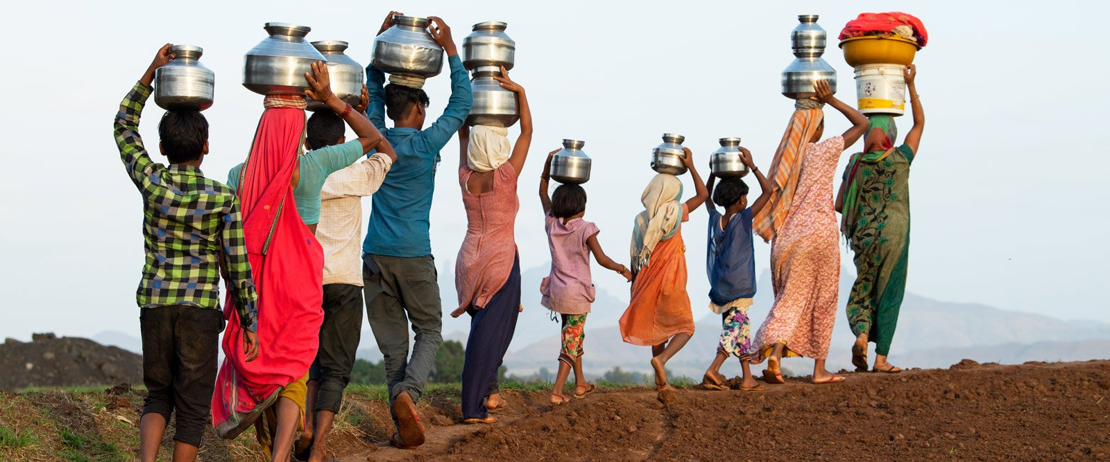 A group of people carry water on their heads in India