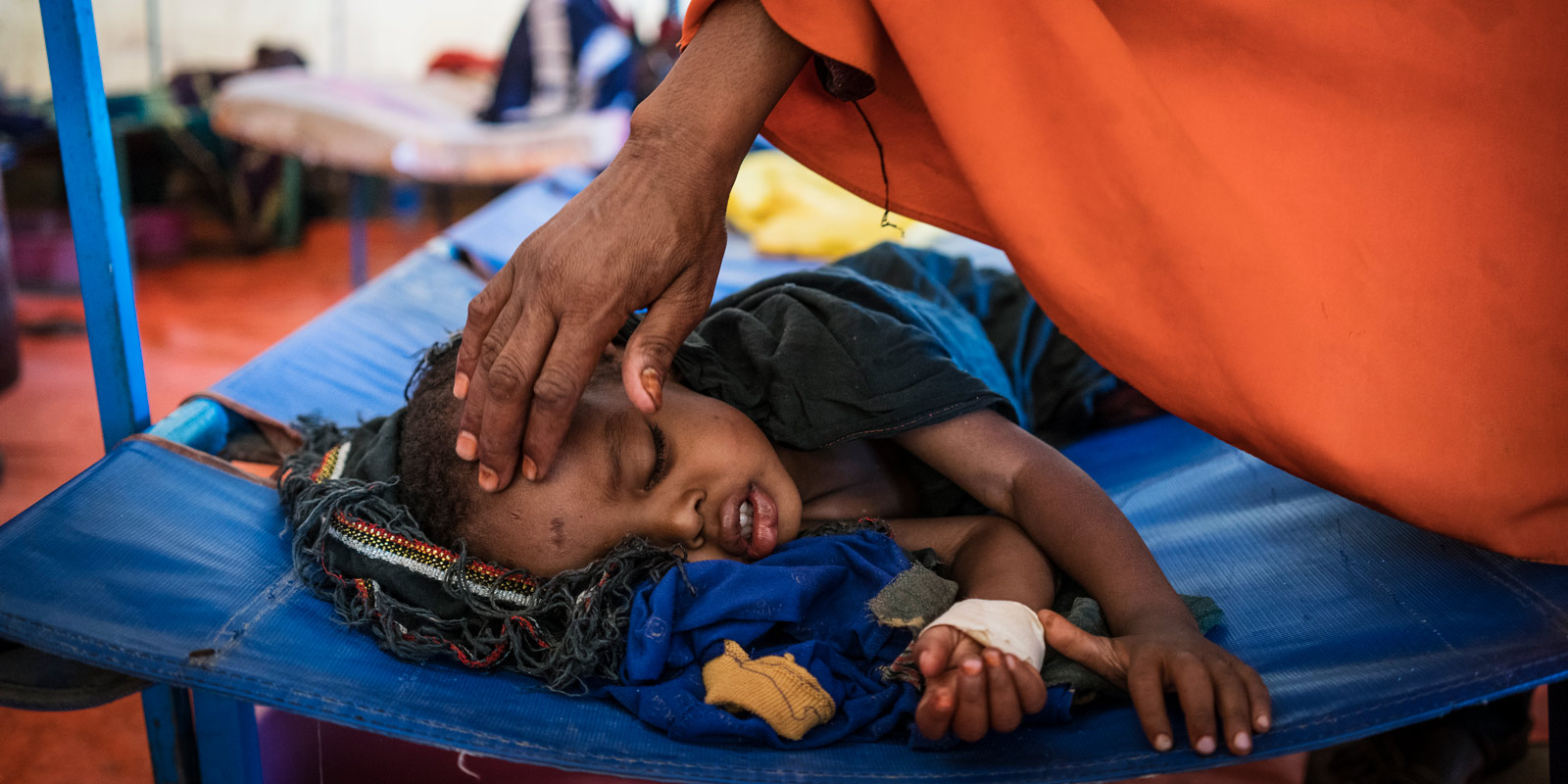 A mother cares for her son who is being treated for cholera at a UNICEF-supported cholera treatment center in Baidoa, Somalia.