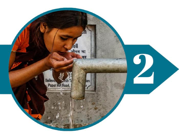 Woman drinking clean water from a Jesus Well