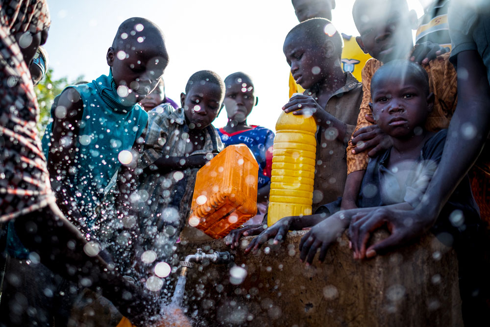 Internally Displaced People fill containers with water at a tap inside the Dalori camp in Maiduguri, Borno State, Nigeria