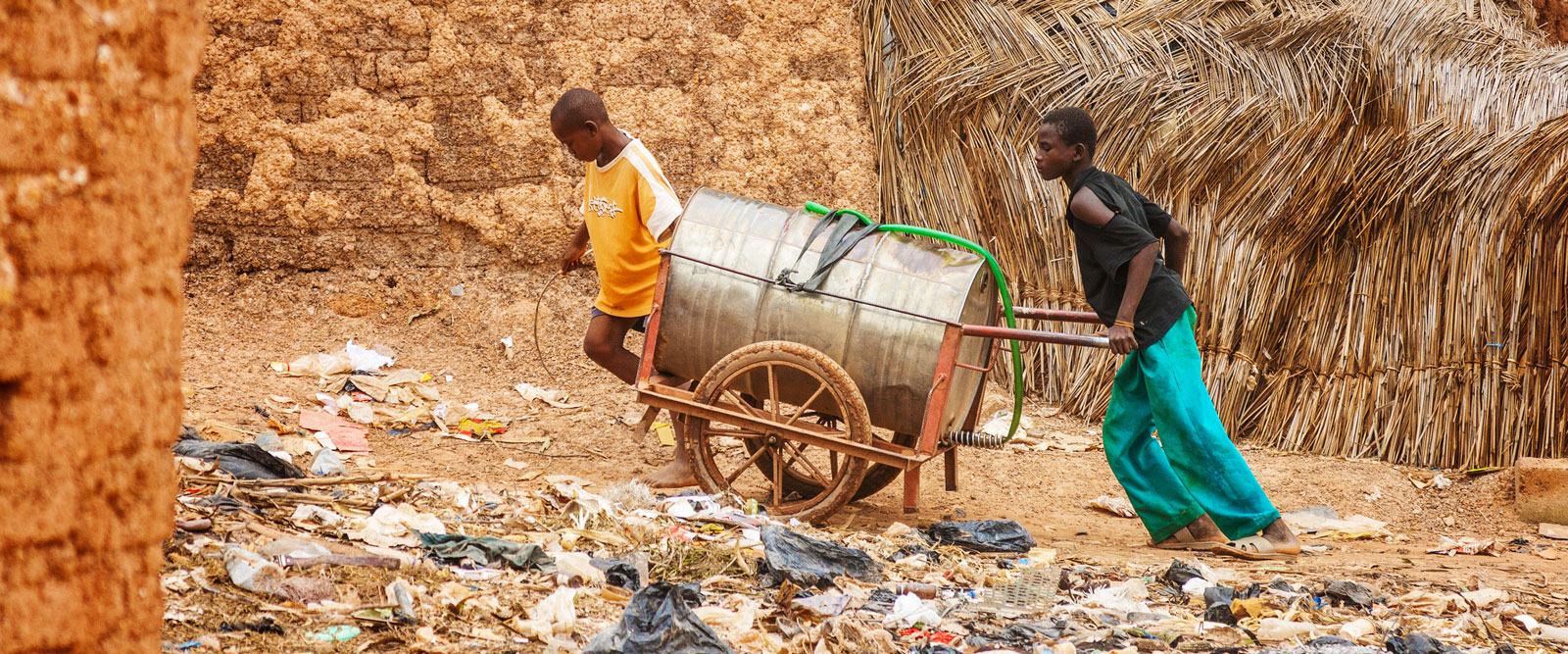 Two young boys towing a can of water in the slums of Ouagadougou in order to distribute water to the inhabitants, Burkina Faso.