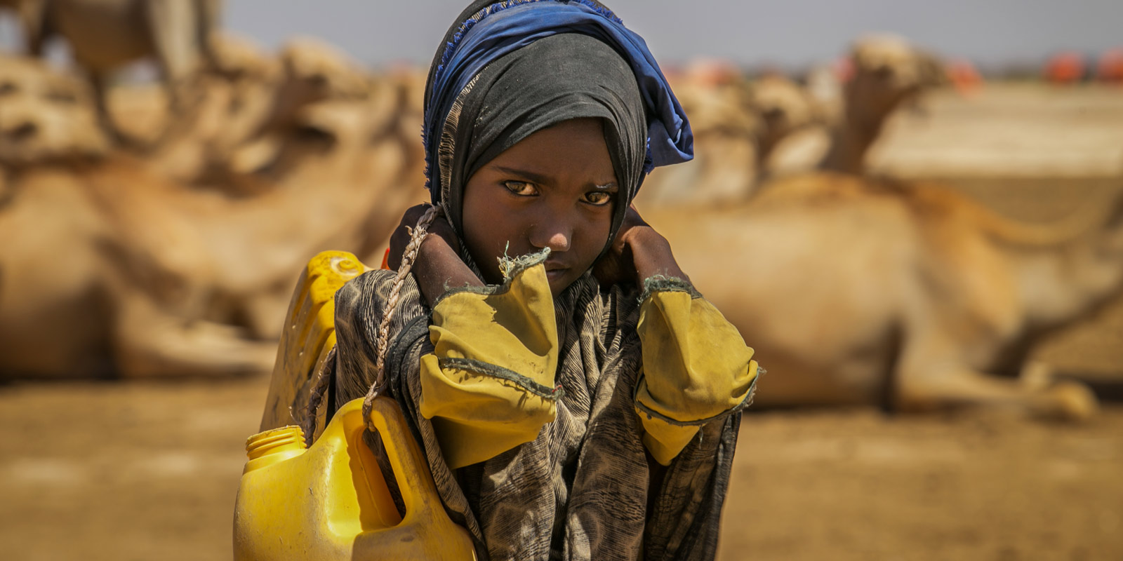 During her school break, 9-year-old Sulem Hire from Ethiopia carries jerry cans to collect water at a borehole four kilometers from her home. This means an eight kilometer walk carrying heavy jugs of water—a heavy task for a young girl.