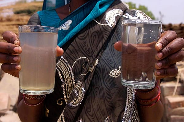 Woman holding glasses of clean and dirty water.