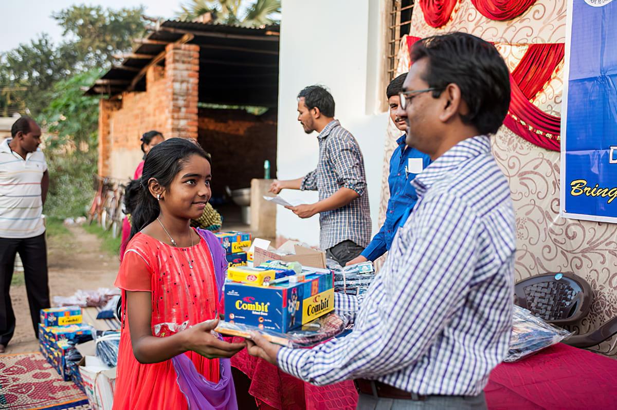 Girl receiving school supplies from Bridge of Hope center