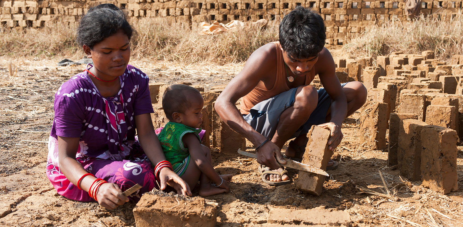 This woman works alongside her husband to make bricks, bringing her infant with her. Both men and women work hard in rural villages to try to make ends meet.