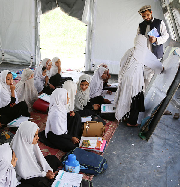 Solutions to Poverty: Girls attend school in a Tent