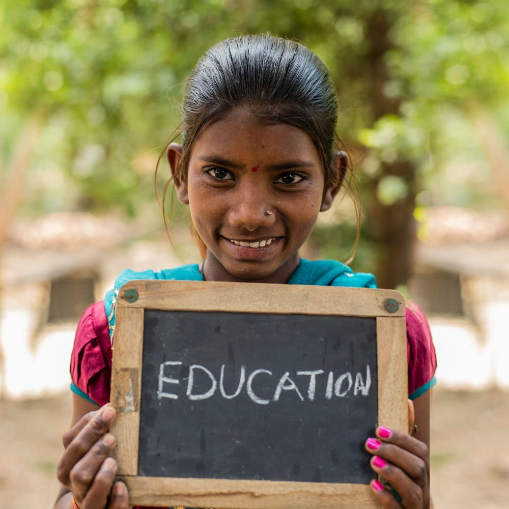 Young girl holding a chalkboard with Education written on it