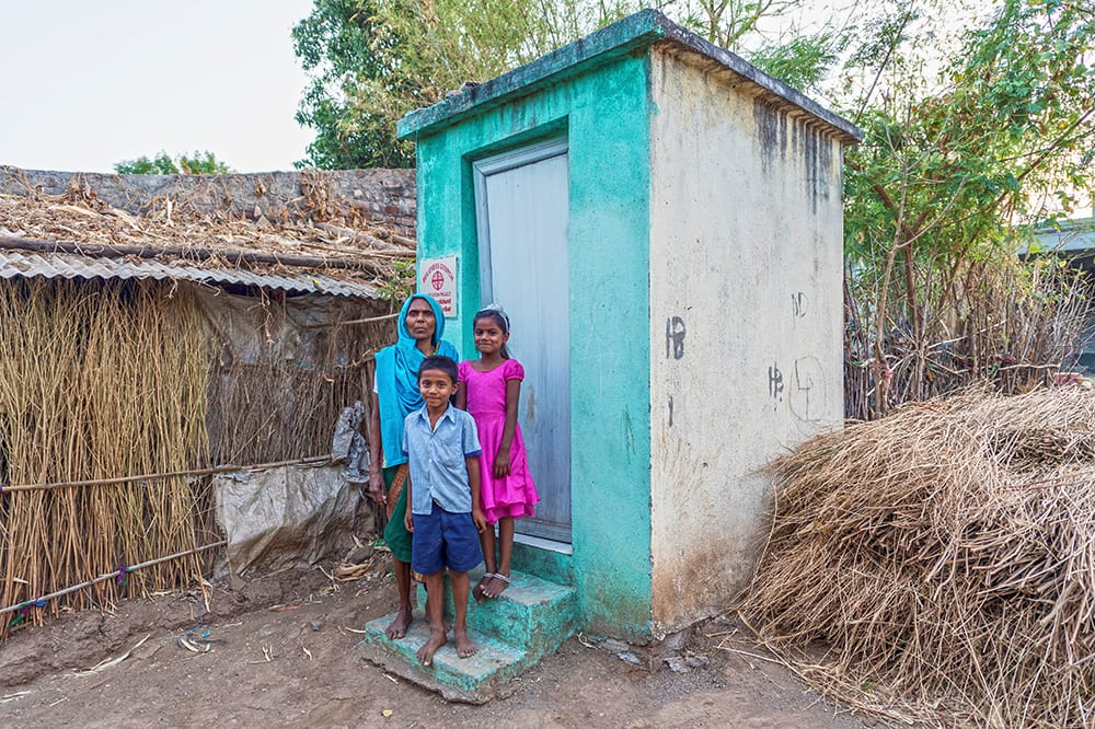 Mother with her son and daughter in front of an outdoor toilet gifted through GFA World donors
