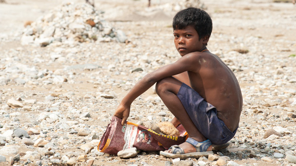 Poverty devastates the whole family, often causing children to drop out of school early to start working. This boy is one of 168 million child laborers doing the backbreaking work of collecting, breaking and selling rocks from a nearby river.