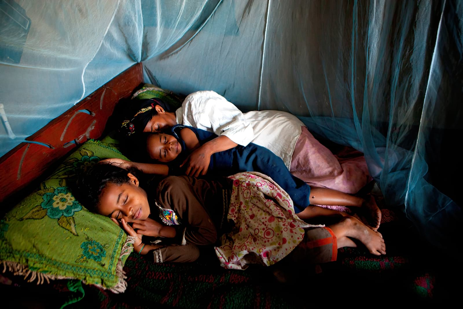Family sleeping inside mosquito net covered bed.