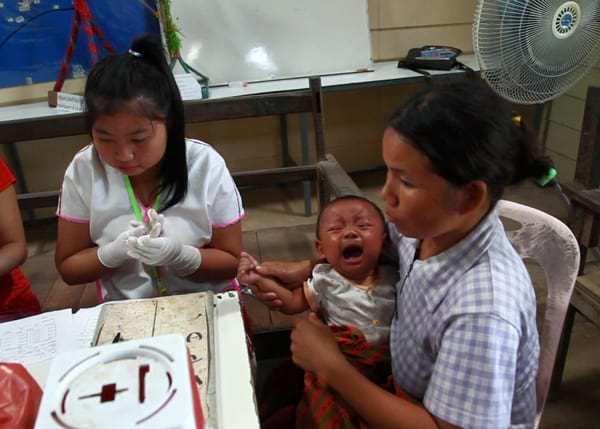 Health workers take blood sample from an infant, testing for malaria.