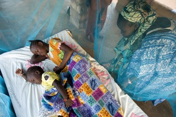 A mother watching her children sleep inside a mosquito net covered bed.