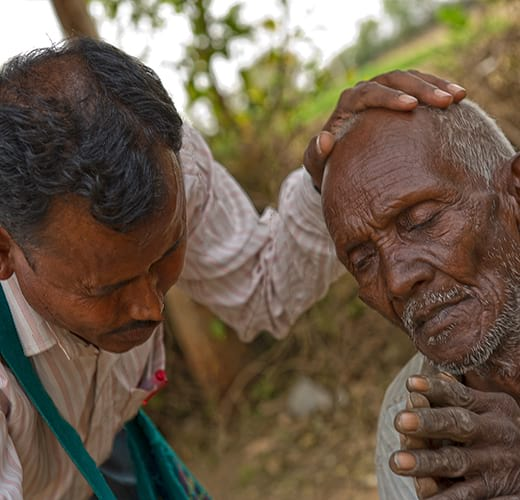 National missionary worker praying for a man