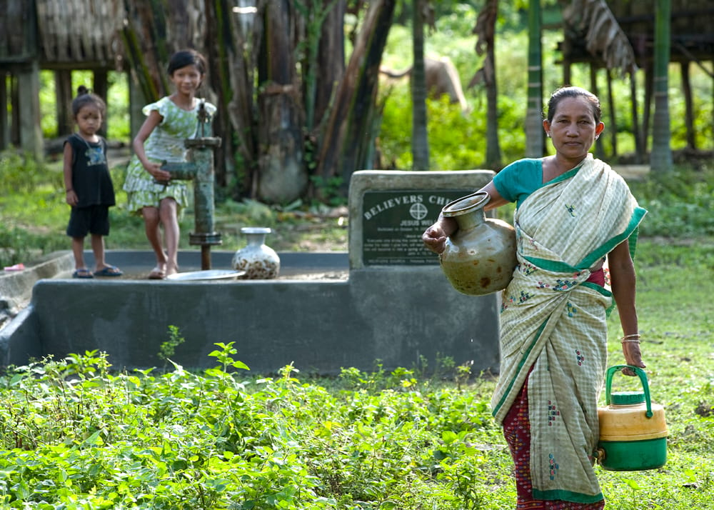 Women and children enjoying clean water from Jesus Wells.