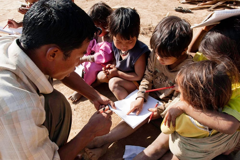 A national missionary worker teaches a group of children how to read
