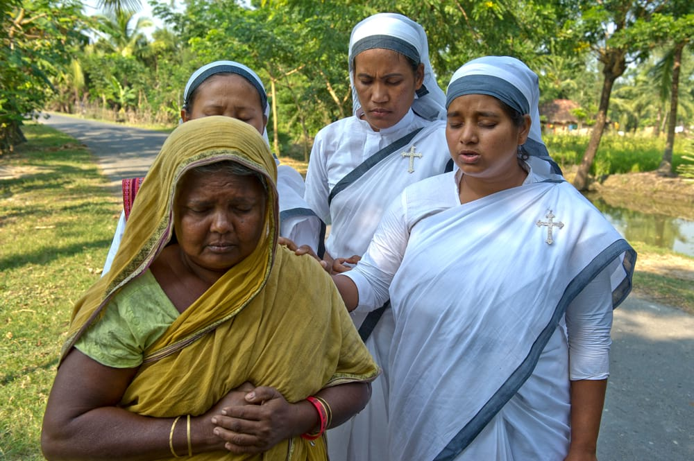 Sisters of Compassion praying for a poor widow