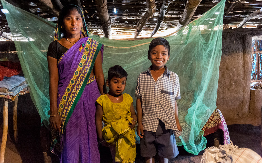 A family in front of their mosquito net