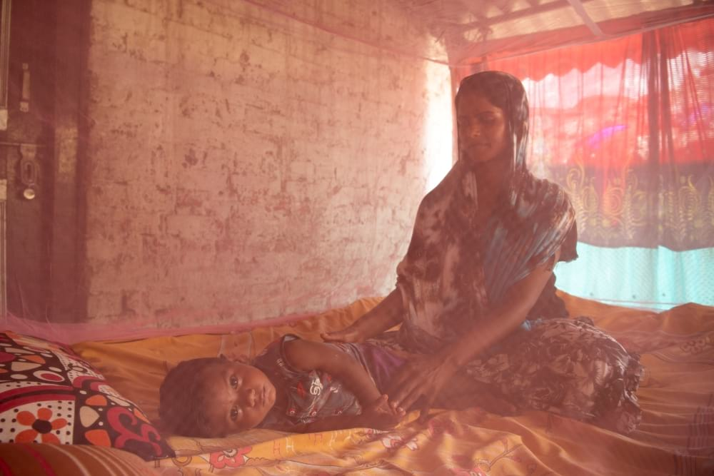 Mother and child resting under mosquito net