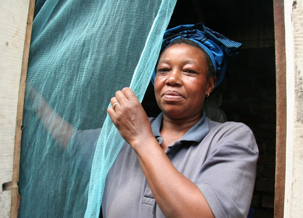 A woman puts up a mosquito bednet.