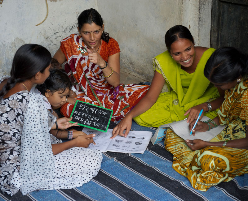 Manju, teaching several women how to read and write in a literacy class.