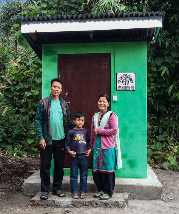 A family in front of a GFA-provided outdoor toilet and sanitation facility