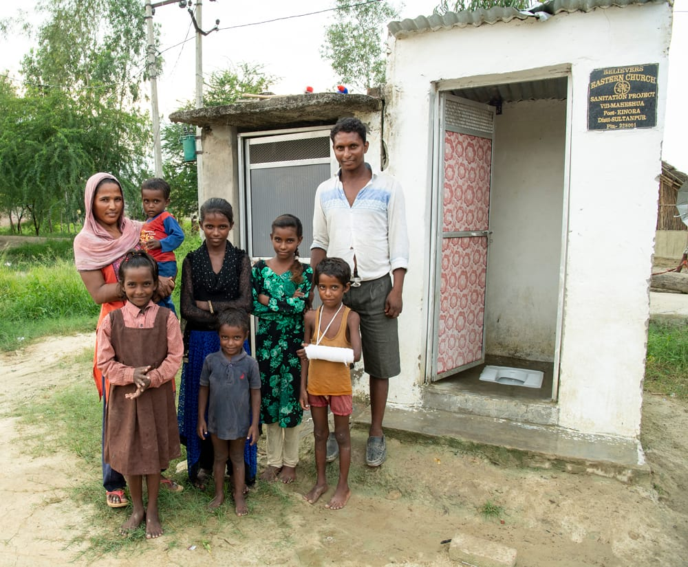 Family standing outside of Outdoor Toilets