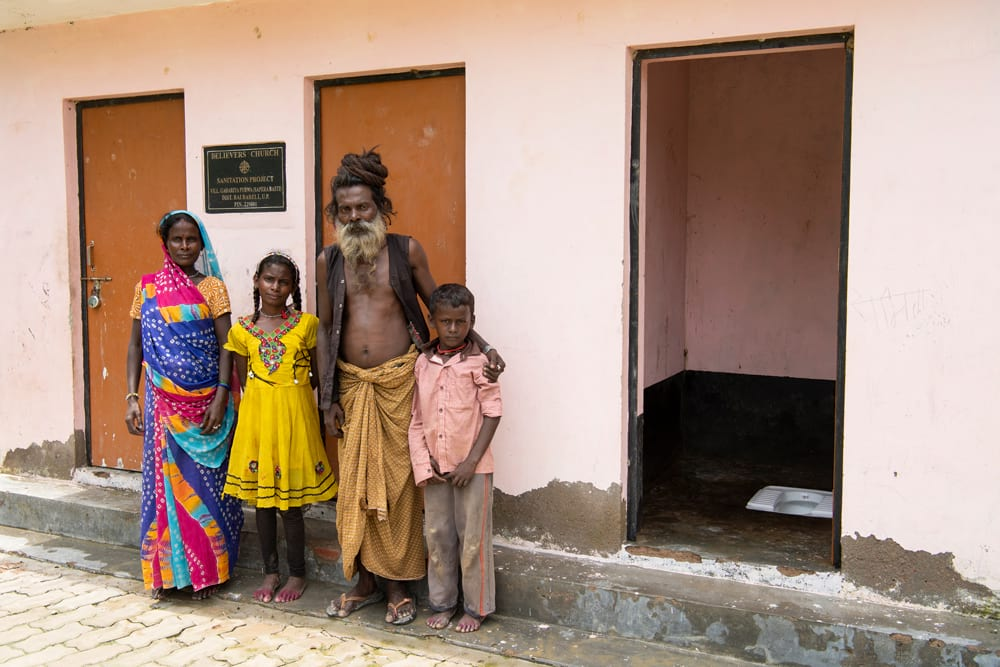Family in front of outdoor toilets built through GFA World donations