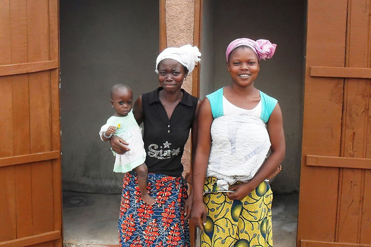 Two women and child outside of outdoor toilet