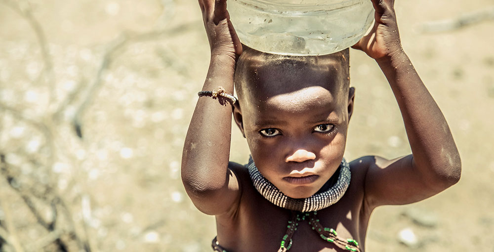 A child of the Himba tribe carries a bucket of water in Kamanjab, Kunene, Namibia
