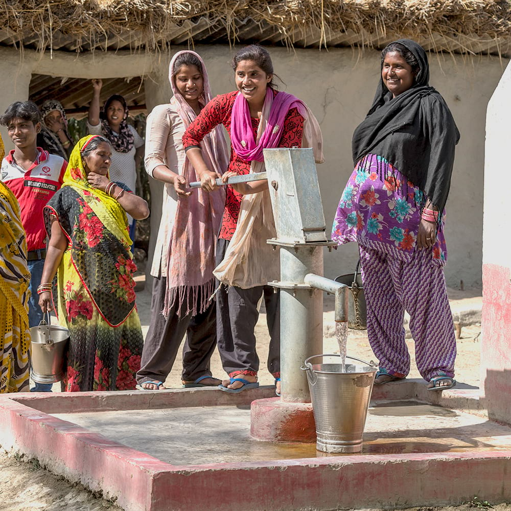 Women drawing clean water from Jesus Well