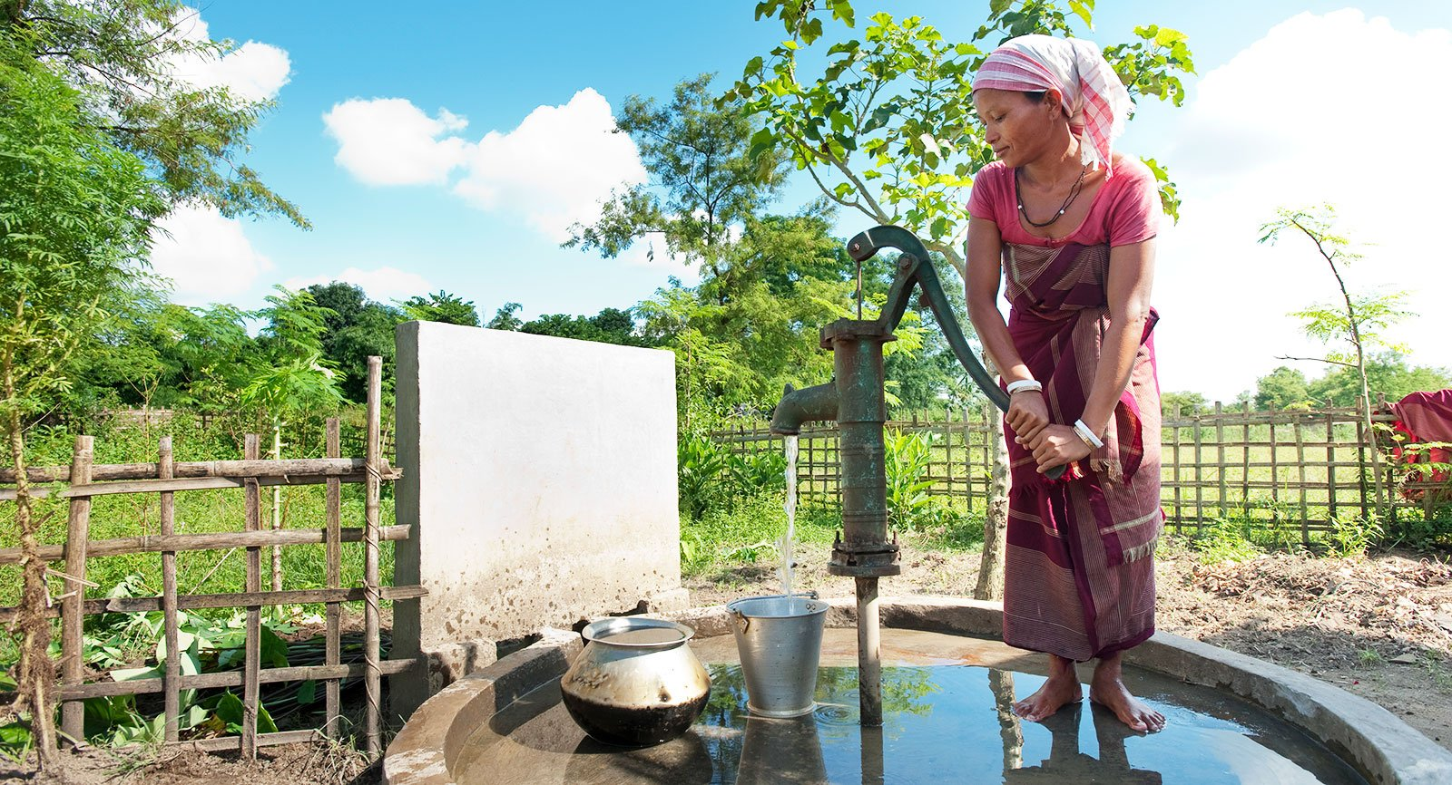 A woman gets clean water from a Jesus Well. India water crisis issues require practical water scarcity solutions to provide people with access to safe drinking water.