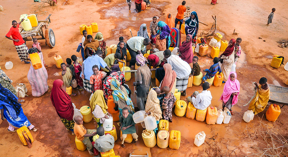 A Picture of the Global Water Crisis where refugees who experience water scarcity are waiting to get clean water and satisfy their thirst in a camp in Dadaab, Somalia.