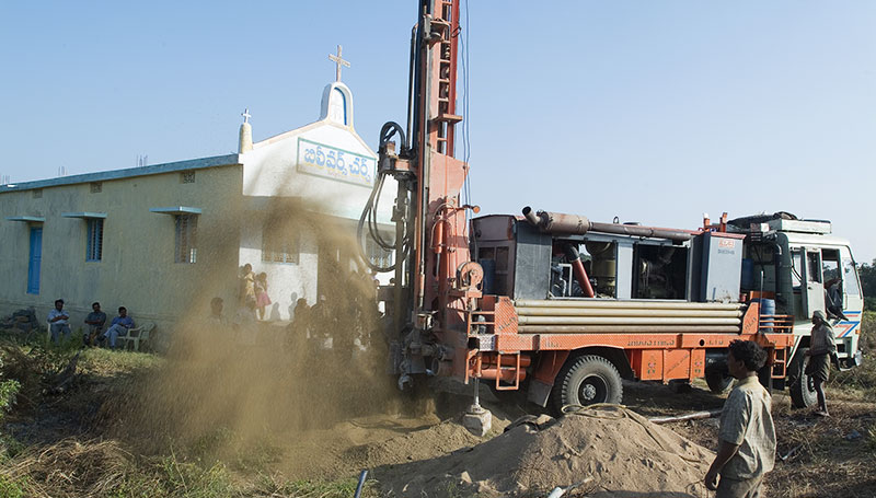 A Jesus Well is being drilled next to a church building. This is the first well dug in the village