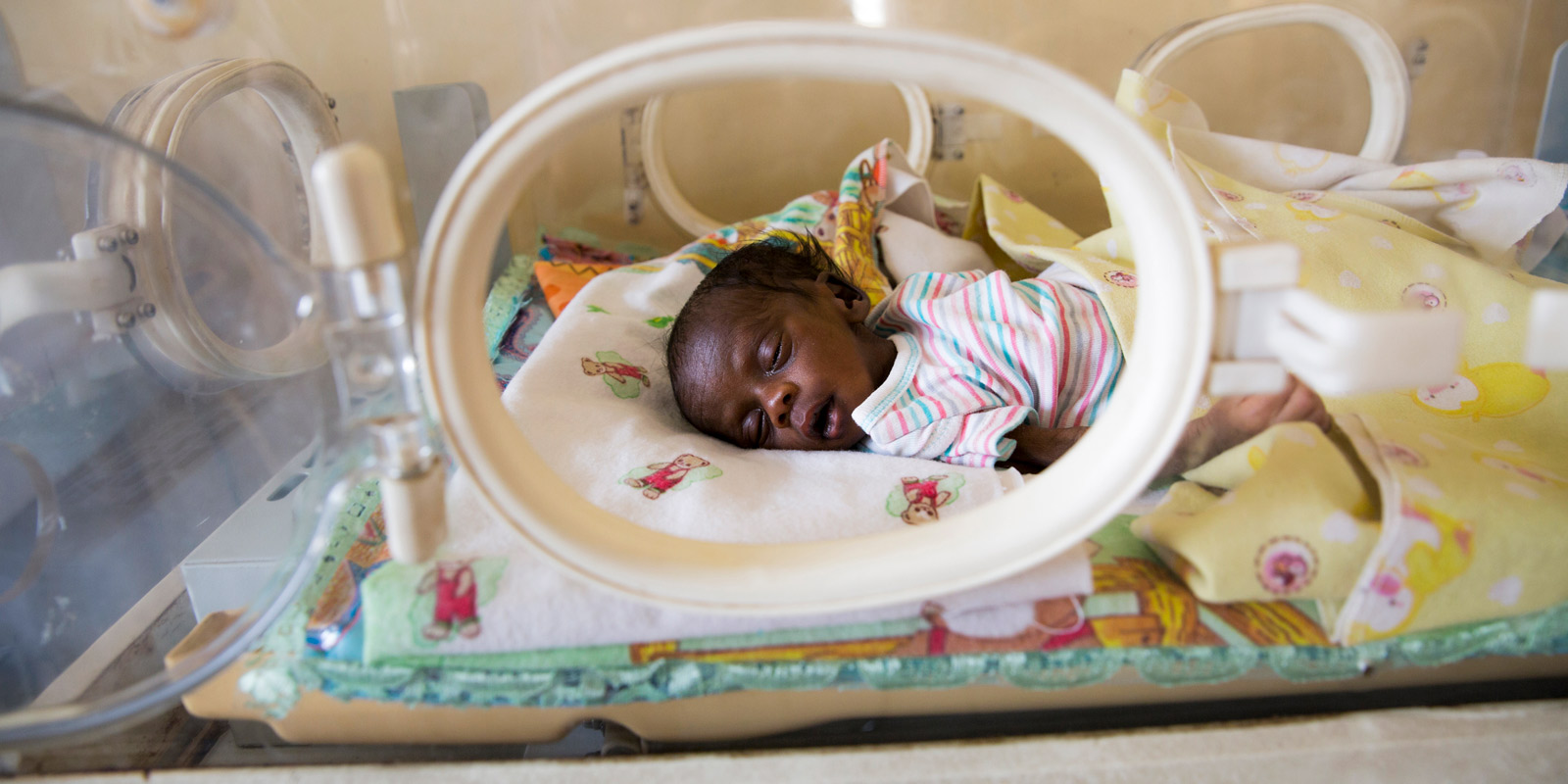 This newborn infant lies in an incubator, suffering from sepsis and jaundice , struggling to survive. His mother died giving birth.