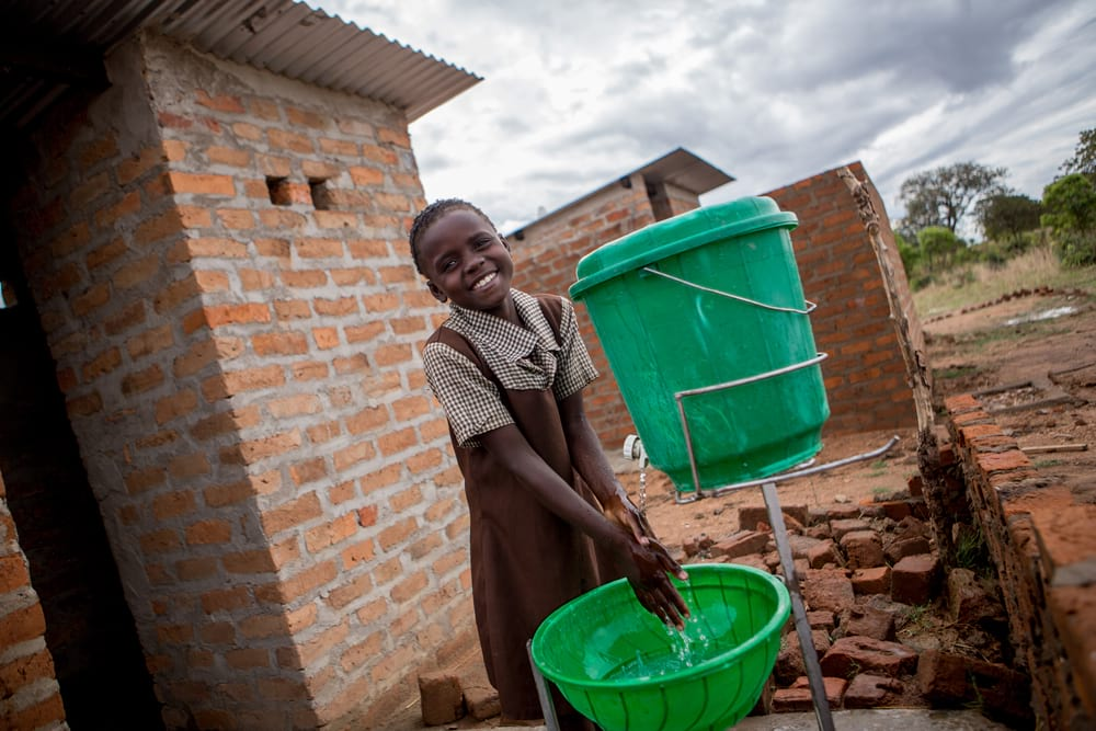 A student washing her hands outside latrines.